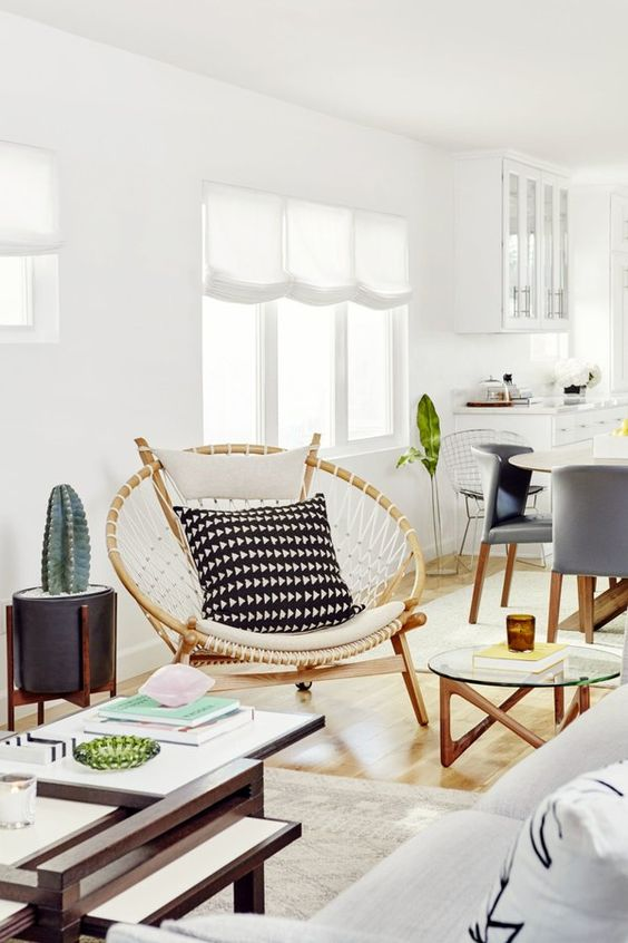 a mid-century modern living room with a neutral sofa, several tables, a papasan chair with pillows and a potted cactus