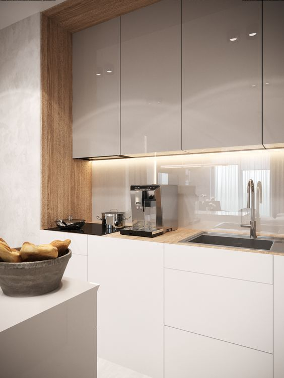 a minimal two-tone kitchen with grey and white cabinets, with a neutral glass backsplash that adds a sleek feel to the space