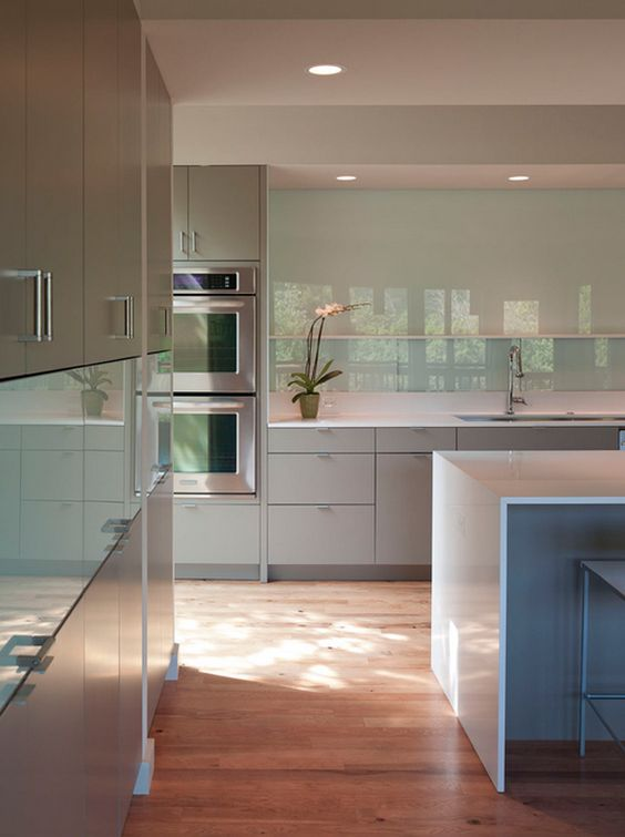 a minimalist grey kitchen with an aqua glass backsplash, a white ktichen island and built-in lights is a perfect space