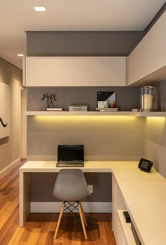 a minimalist home office with a closed wall storage unit and an open shelf, a corner desk and built in lights plus a simple chair