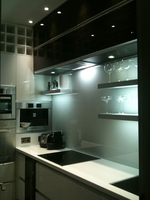 a minimalist kitchen with black and white cabinetry, a light blue glass backsplash, open shelves and built-in lights is small yet functional