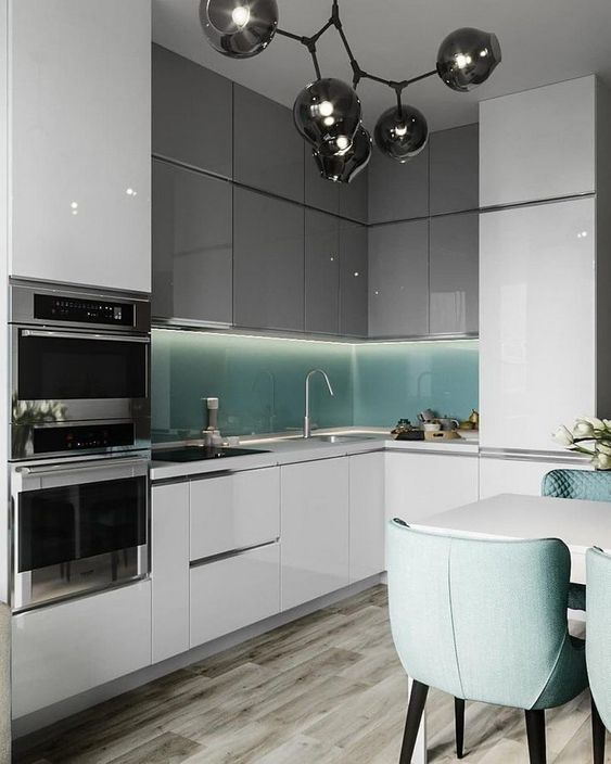 a minimalist two tone kitchen with grey and white cabinetry, a turquoise glass backsplash and matching turquoise chairs