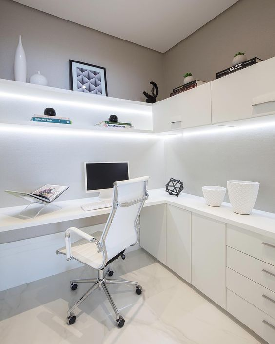 a minimalist white home office with closed and open storage units, a corner desk with closed units, a white chair and built-in lights
