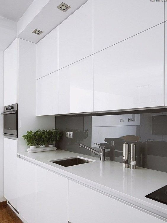 a minimalist white kitchen with a taupe glass backsplash, sleek cabinetry, potted greenery and lights over the space