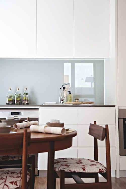 a minimalist white kitchen with sleek cabinets, a light grey glass backsplash and a dining zone with rich stained wooden furniture