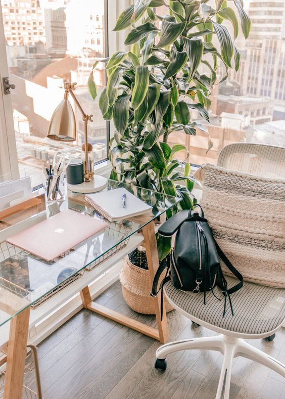 a modern boho working space with a glass and wood desk, a comfy chair, a boho pillow and a potted plant, glazed walls for amazing views