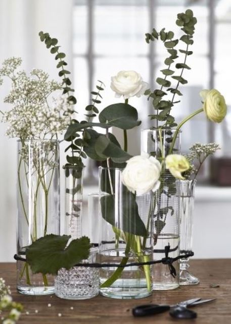 a modern cluster centerpiece of mismatching glass vases, eucalyptus, white blooms is a stylish and cool idea to recreate
