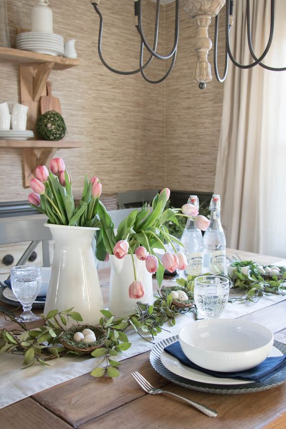 a modern farmhouse Easter table with a neutral runner, navy napkins and white porcelain, pink tulips and nests with eggs