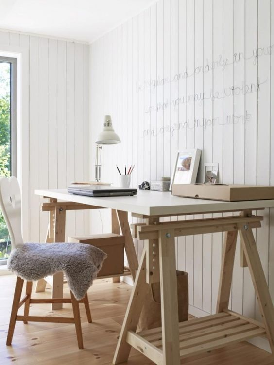 a modern farmhouse home office with a trestle desk, a matching chair, a table lamp and neon lights on the wall