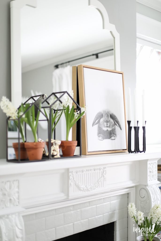 a modern farmhouse mantel with house-shaped frames with blooms, a bunny and a bunny print plus candles