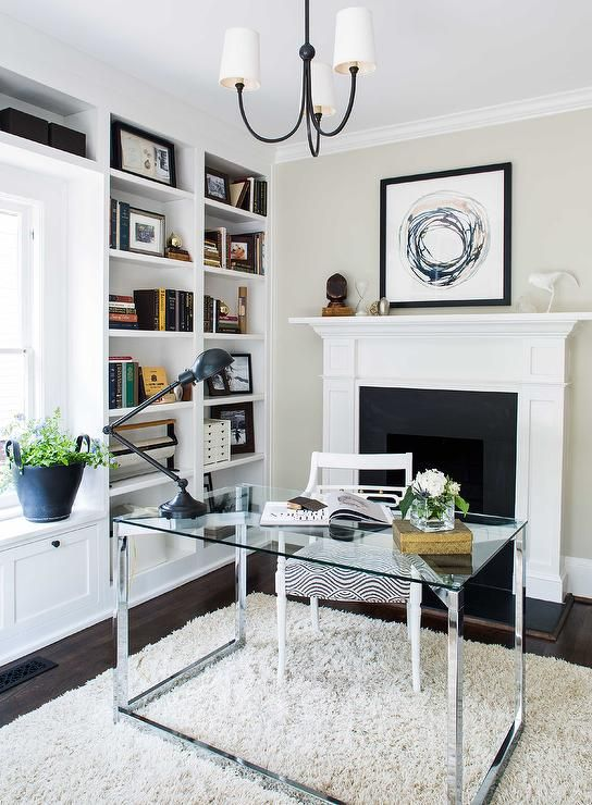 a modern home office in neutrals, with built in storage units, a glass and metal desk, a catchy chair and a non working fireplace