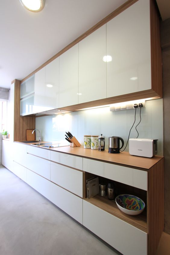 a modern kitchen with sleek white cabinets and light stained wooden surfaces, with built-in lights and niches for storage
