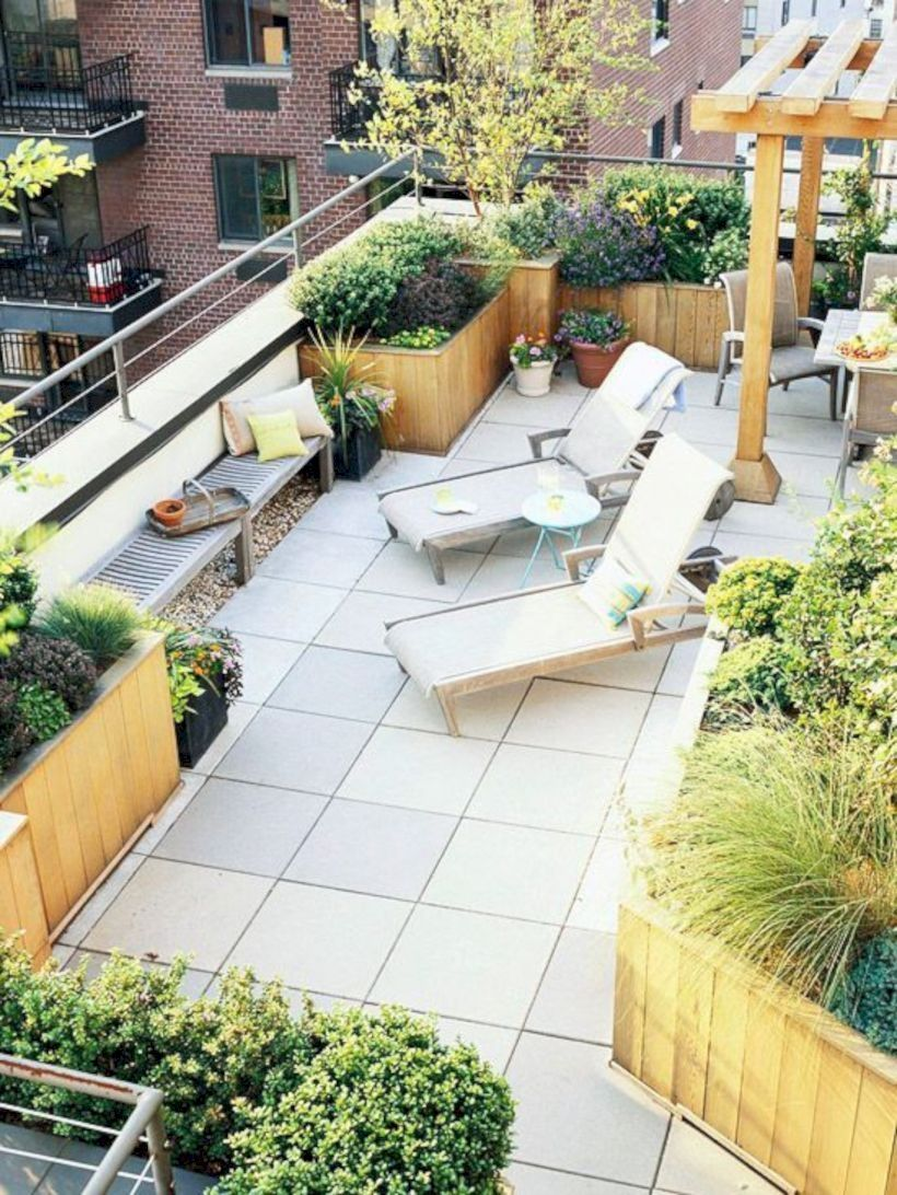 a modern rooftop terrace with tiles on the floor, a bench, loungers, a dining zone and potted plants everywhere