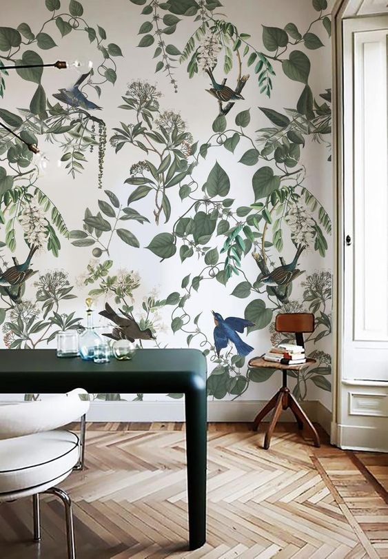 a modern space with beautiful botanical wallpaper, a hunter green table, a white chair, a small stool and carafes