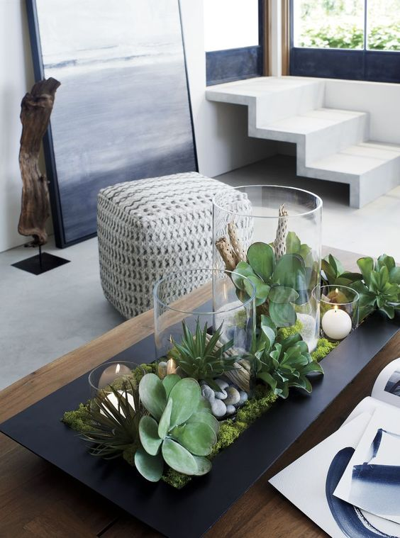 a modern spring centerpiece of a black tray, moss, succulents, eucalyptus, candles and pebbles is a bold and non-typical idea
