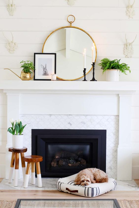 a modern spring mantel with a round mirror, greenery in a pot and a watering can, candles and a bunny print in a frame