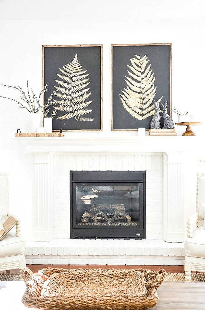 a modern spring mantel with bold graphic prints, bunny figurines, blooming branches and a tray is cool