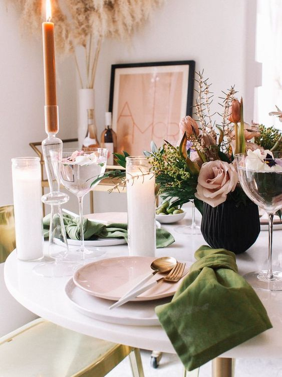 a modern spring tablescape in pink and green, with a floral centerpiece, green napkins and pink plates plus candles