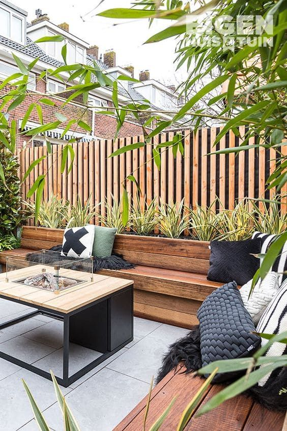 a modern spring terrace with a rich-stained corner seating, a fireplace table and potted plants and trees