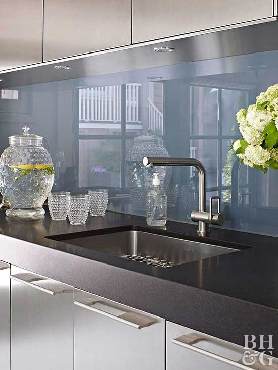 a modern stainless steel kitchen with a blue glass backsplash. black stone countertops and built-in lights is very bold