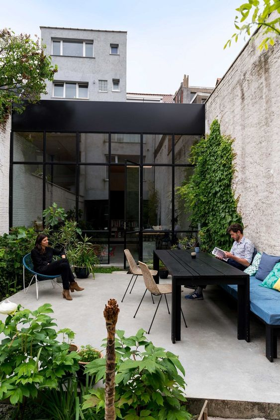 a modern terrace with a black table, upholstered bench with pillows, chairs and greenery everywhere