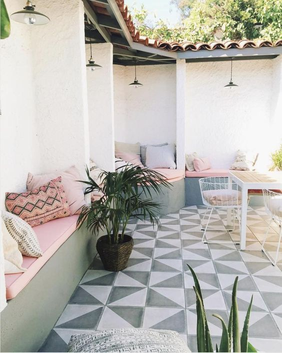 a modern welcoming spring terrace with a geometric floor, built-in concrete benches with pink cushions and potted greenery