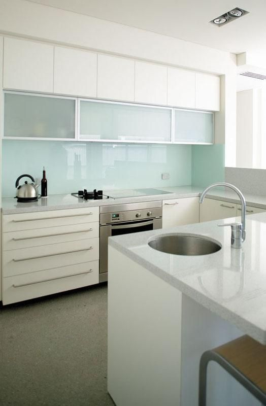 a modern white kitchen with a light blue glass backsplash, frosted glass cabinets and stainless steel handles