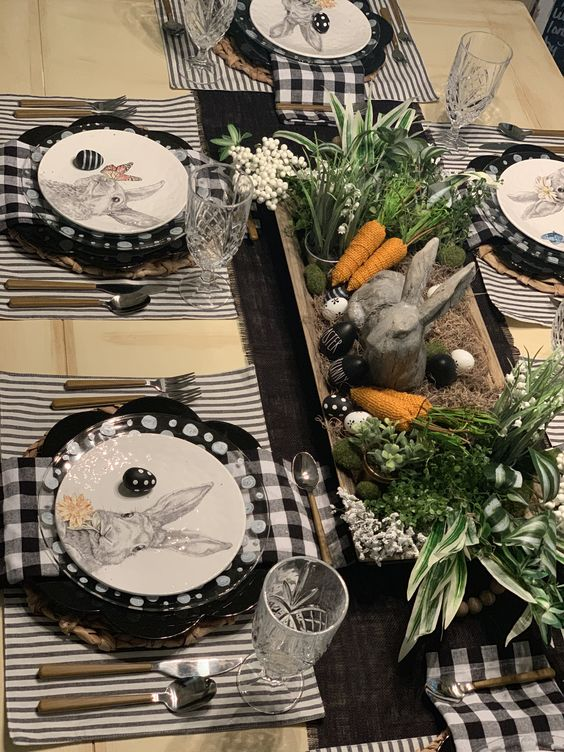 a monochromatic Easter tablescape with plaid and striped linens, greenery, burlap carrots, bunnies and eggs