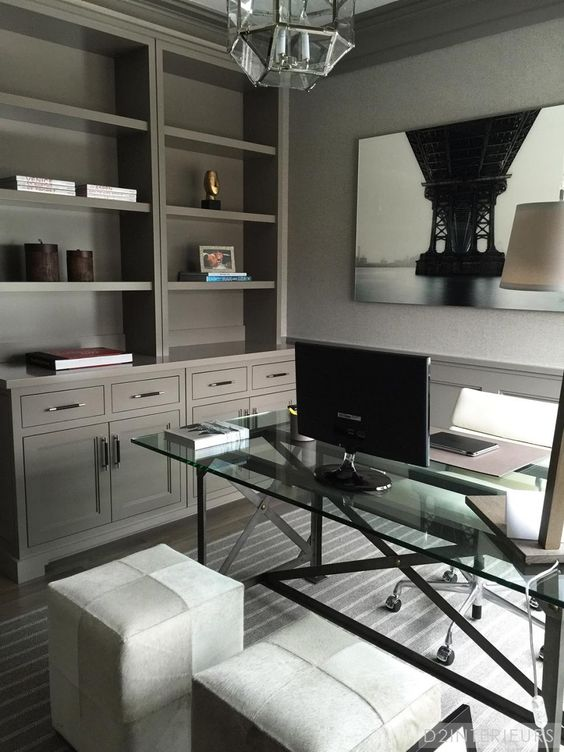 a moody home office with a large built-in storage unit, a glass and metal desk, ottomans and a chair on casters plus a faceted lamp