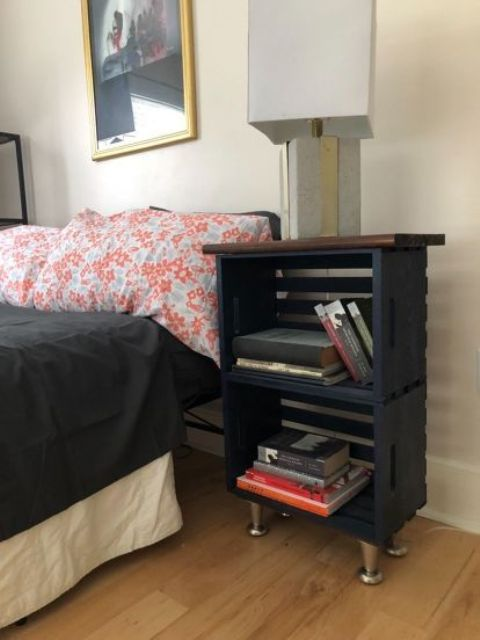 a navy nightstand made of two crates, with a stained top and metal legs plus a lamp with a concrete base lamp