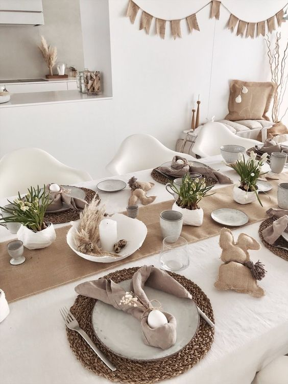 a neutral Easter tablescape with a burlap runner, woven chargers, neutral linens, burlap bunners, potted blooms and candles