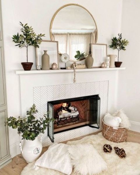 a neutral boho mantel with potted plants, wooden beads, vases, prints in frames and a round mirror plus greeneyr in a jug