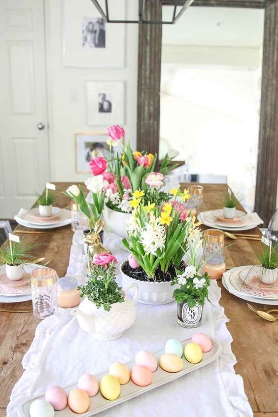 a pastel Easter table setting with potted greenery and blooms, candles, greenery in egg shells and pastel eggs