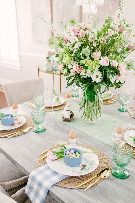 a pastel Easter tablescape with a pink floral centerpiece, blue and green linens, green glasses and blue cups with candies plus eggs