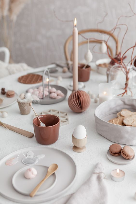 a pastel Easter tablescape with grey, white and terracotta porcelain, candles, pink sugar eggs and bunnies