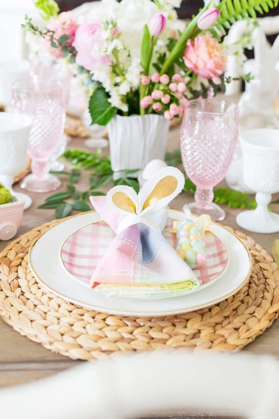 a pastel Easter tablescape with woven chargers, plaid plates, colorful napkins, pink and white blooms and pink glasses