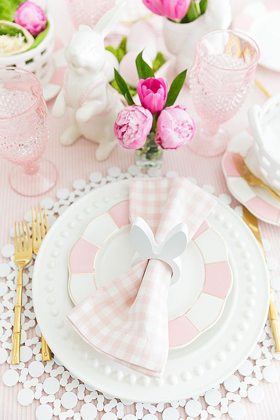 a pink and white Easter table setting with plaid plates and napkins, a cool placemat, pink glasses, blooms and porcelain bunnies