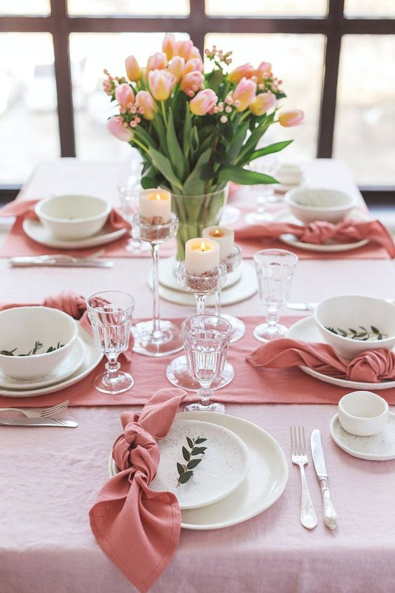a pink spring tablescape with speckled plates, candles in tall candleholders and pink tulips in a vase is a very cool idea