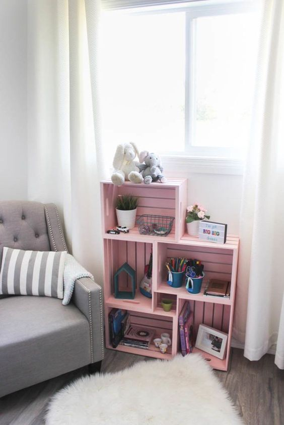 a pink storage unit made of crates, with toys, plants and other stuff is a cool and fun piece for any nursery