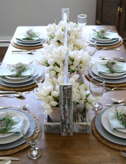 a pretty Easter tablescape with rustic touches, white tulips, woven placemats, blue and white porcelain and eggs with greenery wreaths