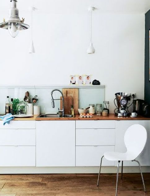 a pretty Scandinavian kitchen with sleek white cabinets, an aqua glass backsplash and a stained wooden countertop plus pendant lamps