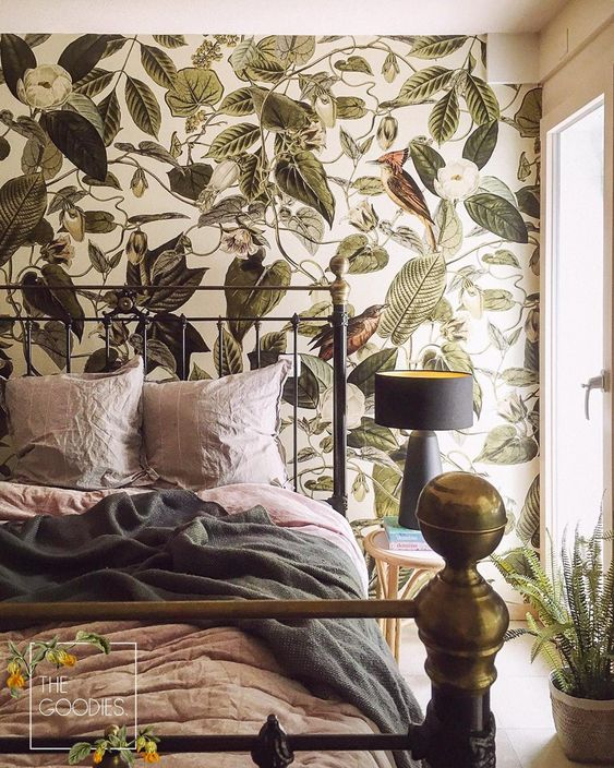 a pretty bedroom that feels refined and tropical thanks to bold leaf print wallpaper and a heavy metal bed