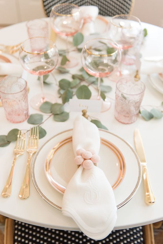 a pretty blush and white spring tablescape with gold cutlery, eucalyptus, pink glasses and pompom napkin rings