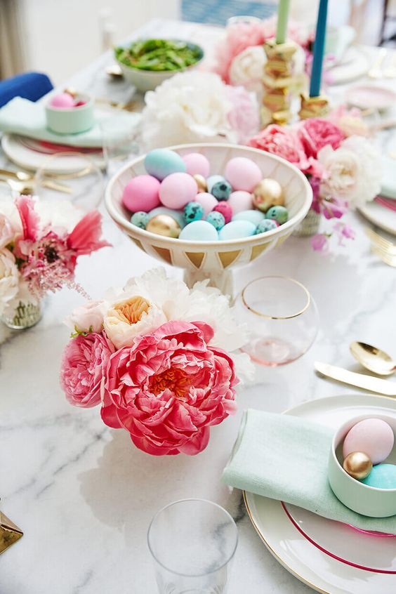 a pretty bright Easter table setting with bold blooms, colorful eggs in a bowl, mint napkins and pastel eggs in a cup