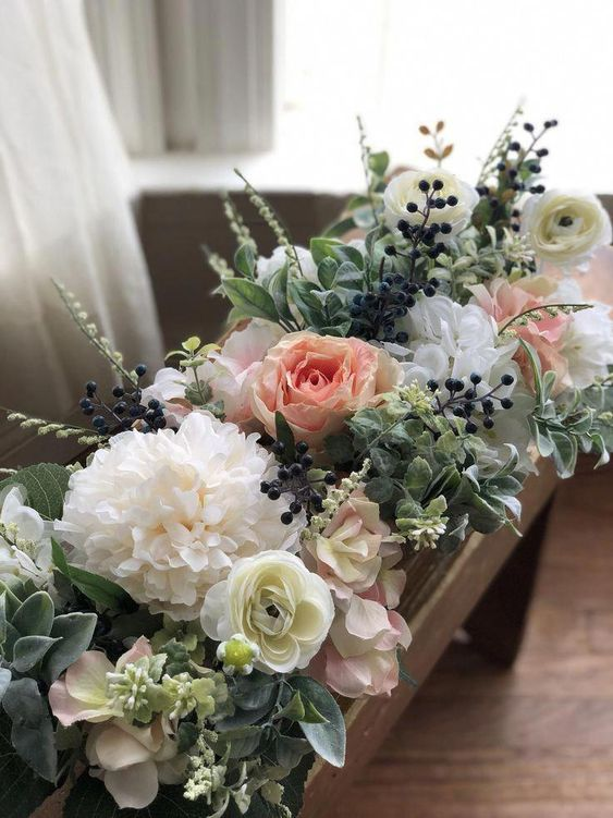 a pretty rustic floral arrangement with white and pink blooms, berries and greenery in a wooden box is a lovely idea of a centerpiece
