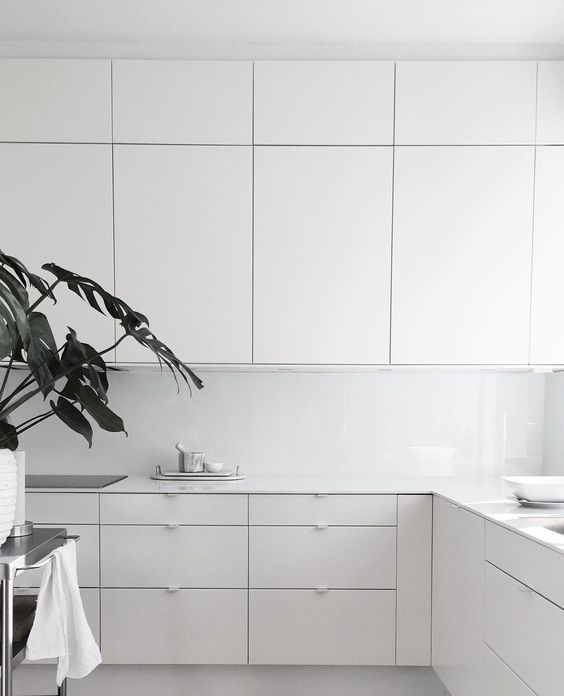 a pure white minimalist kitchen with sleek cabinets and a white glass backsplash is a very airy and light-filled space with much taste