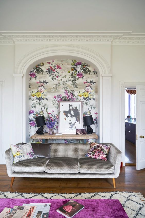 a refined and bold living room accented with chic floral wallpaper and matching pillows is very cool and welcoming