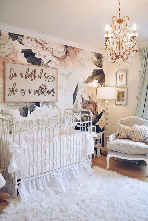 a refined and chic vintage-inspired nursery with pink floral wallpaper, neutral furniture, a crystal chandelier and lovely artworks