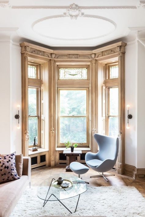 a refined bay winow with decor and detailing, a chair and a footrest for reading here and some plants and decor