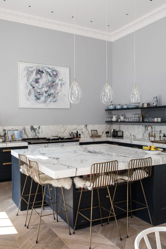 a refined contemporary kitchen with dark cabinets, white marble countertops, a large kitchen island with a sitting zone